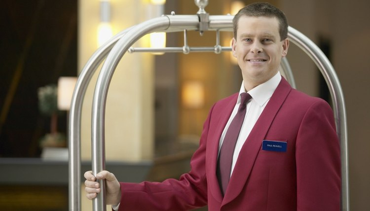 Portrait of a Hotel Doorman in Uniform Standing Next to a Trolley