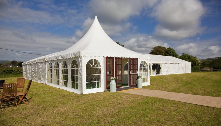 Bright white wedding tent set up on green field.