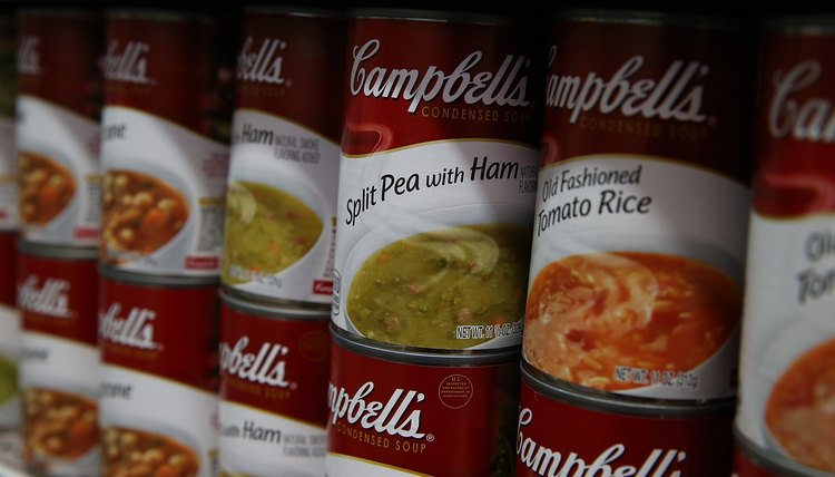 Close-up of a variety of Campbell's Soup cans on a shelf.