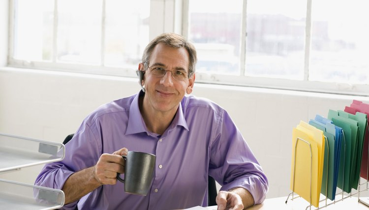 Businessman wearing wireless headset and holding cup of coffee