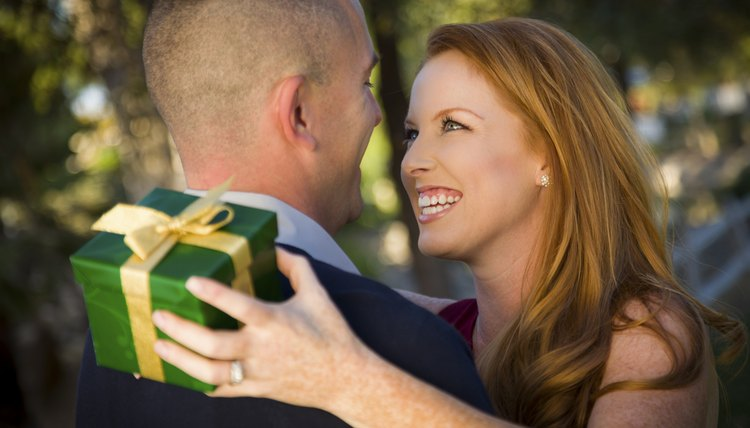 A military man and a smiling woman are exchanging gifts.