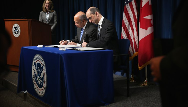 A Homeland Security official signing a foreign policy contract with a Prime Minister.