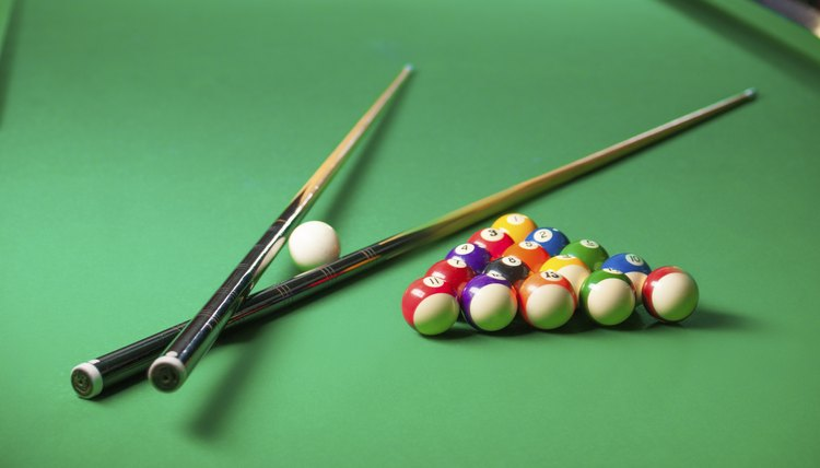 Pool table with cues and balls.