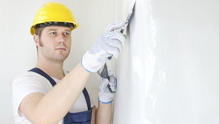Superior Male Builder Repairs Wall With Spackling Paste