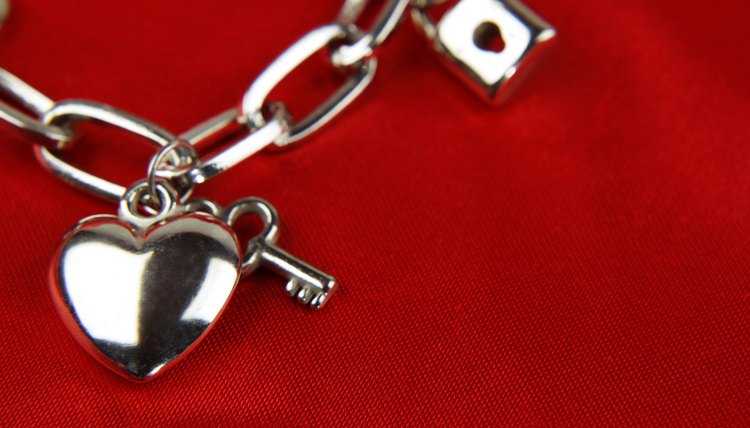 Charms on a charm bracelet, laying on red fabric.
