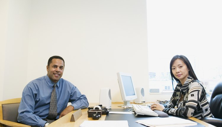 Portrait of a businessman and businesswoman sitting at a desk in an office