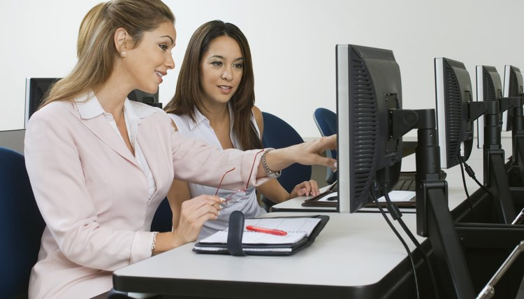 Two business women sitting in computer classroom