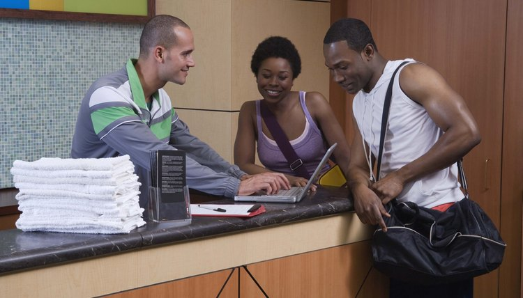 Gym employee helping couple at front desk