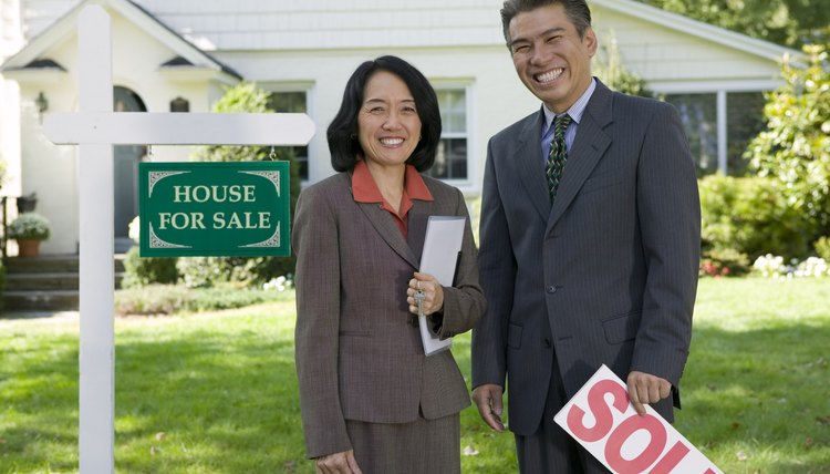 Real estate agents standing by a House for sale sign