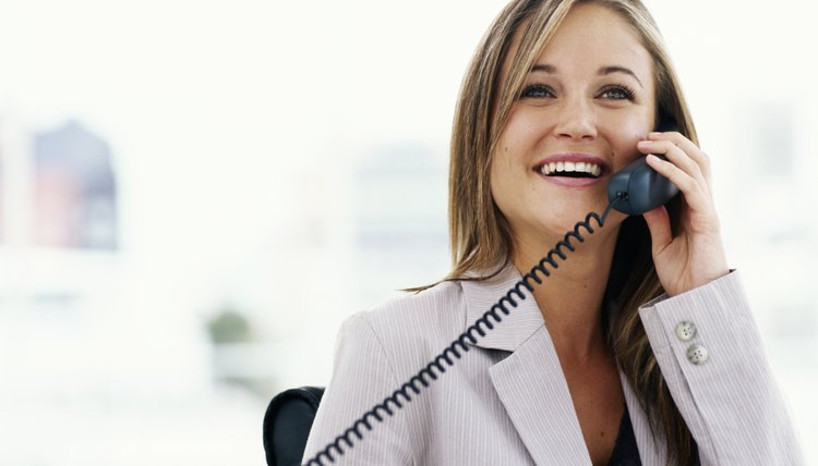 Young businesswoman using telephone in office, smiling
