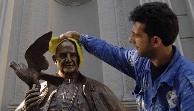 In Istanbul a worker cleans a statue of Pope John XXIII, father of Vatican II.