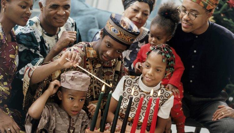 Family celebrating Kwanzaa while lighting the seven Kwanzaa candles