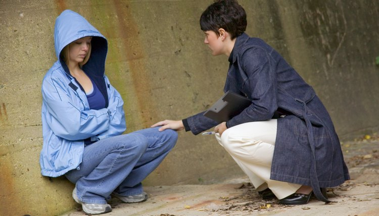 Social worker talking with frightened homeless girl