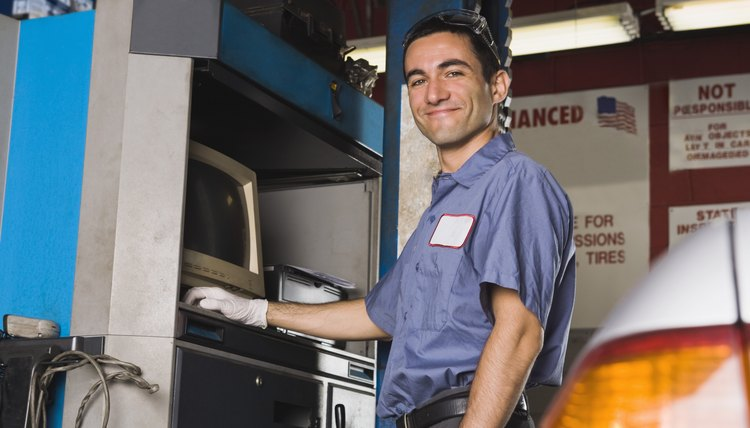 Smiling mechanic with diagnostic computer
