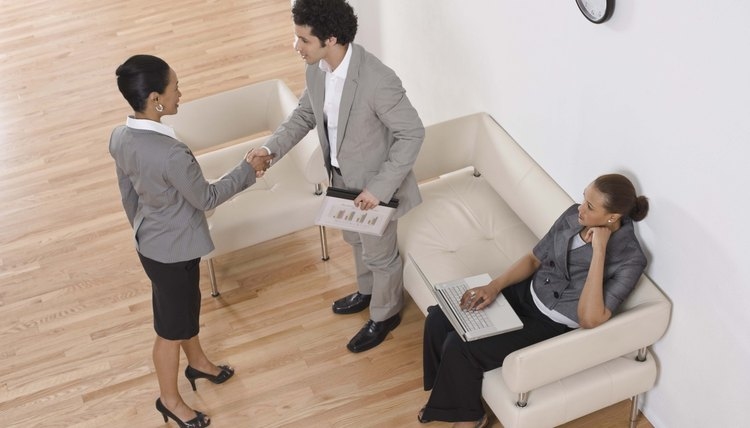 Businesspeople shaking hands in waiting area