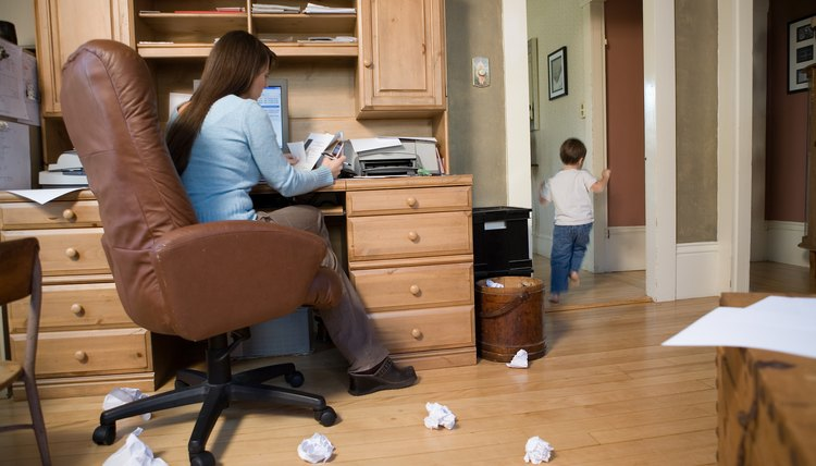 Mother working in home office while boy plays