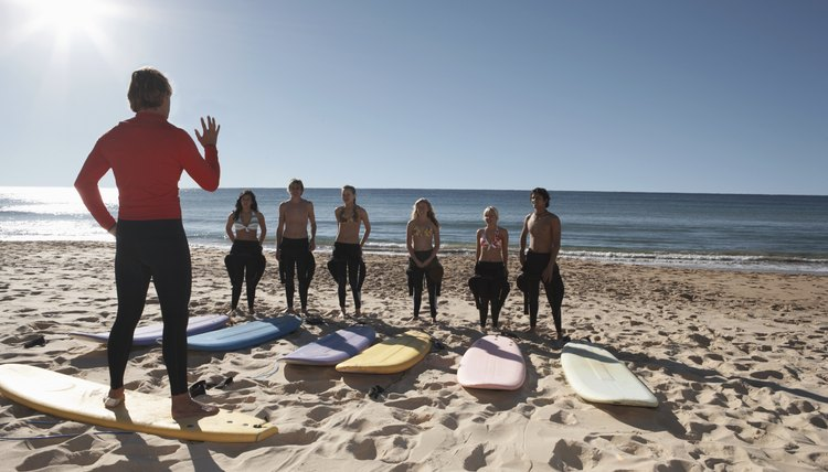 Male surfing instructor on board on beach giving lesson to group