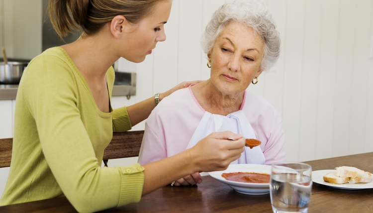 Woman feeding older woman