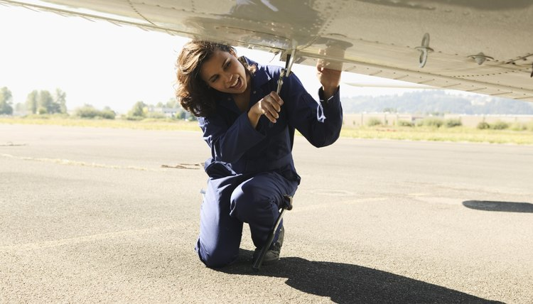 Female mechanic working on underside of airplane wing