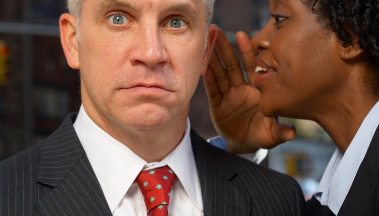 Businessman reacting with surprise to whispering businesswoman