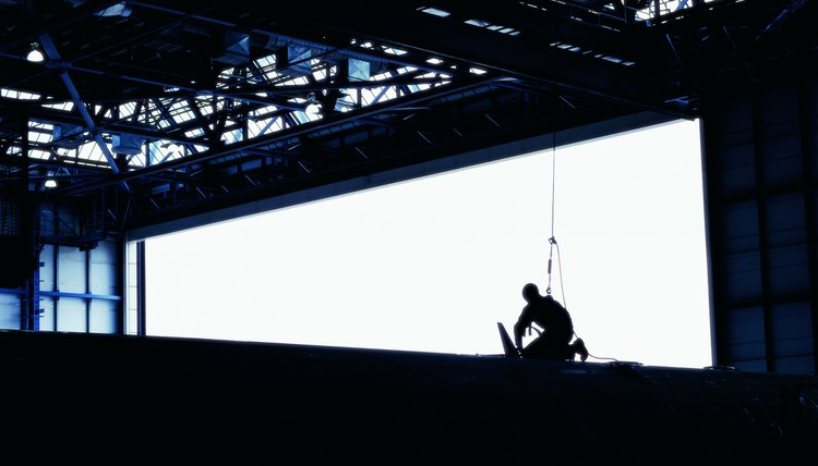 Worker on the top of an airplane working in a hanger