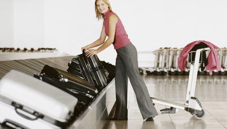 Business Woman Picking Up Luggage from Airport Baggage Collection