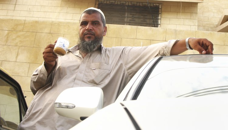 Muslim man standing outside drinking coffee