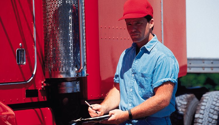 Trucker standing next to semi-truck holding a clipboard