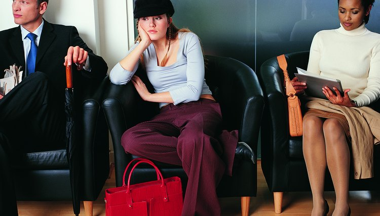 Bored, Female Teenager Sitting in an Armchair Between Two Business Executives Waiting for an Interview