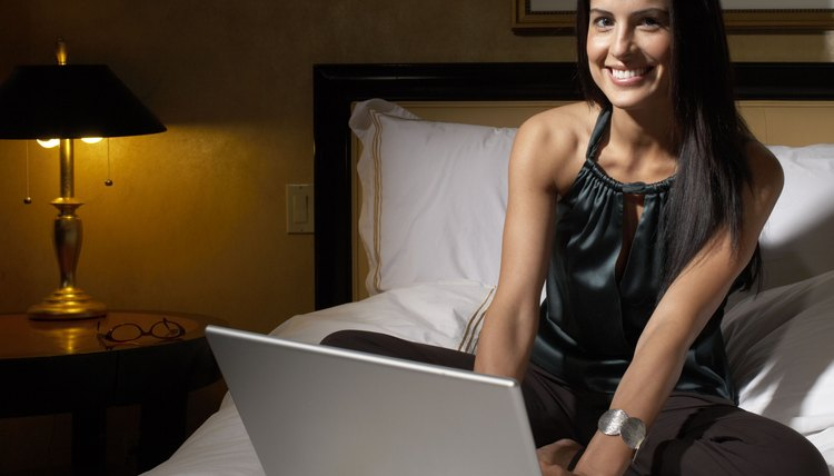 A woman, the bed, her laptop