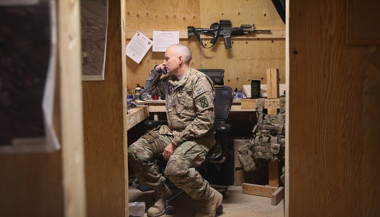 A soldier answers the telephone in an office.