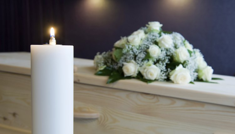 A burning candle next to a casket covered in flowers at a funeral home.