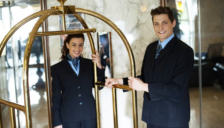 Hotel attendants posing while holding the cart
