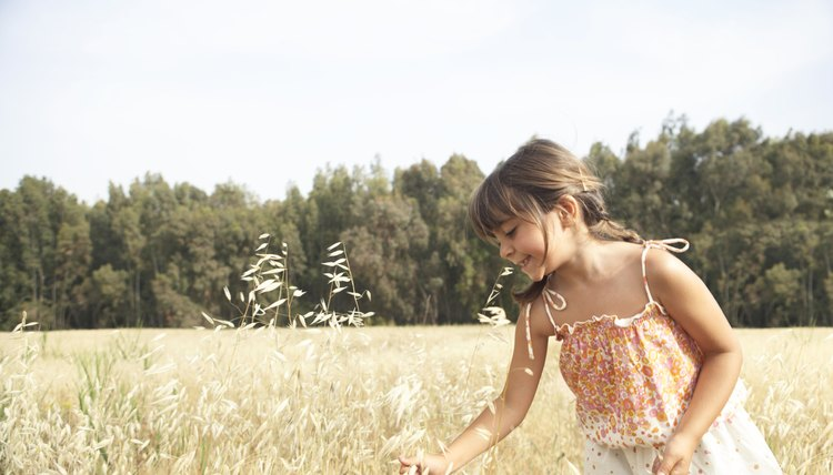 Girl (4-6) in field picking stalks of wheat, smiling, side view
