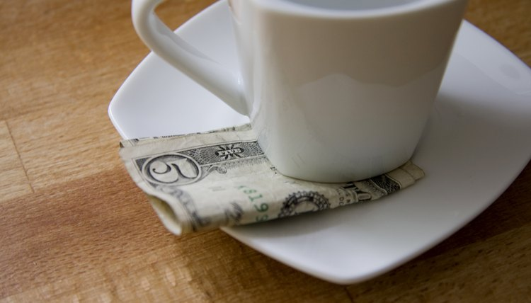 A five dollar bill tucked beneath a coffee cup in a cafe.