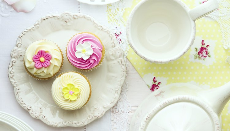 An overhead view of a pretty cupcakes on a plate next to a tea pot and cup.