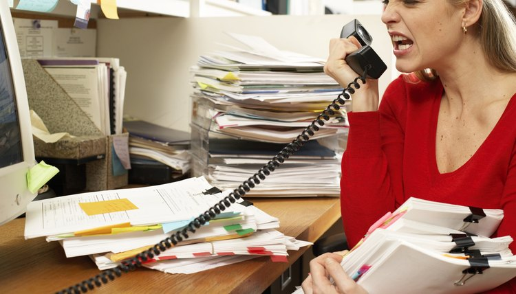 Female office worker holding paperwork, snarling at phone handset