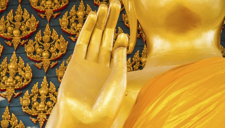 A close-up of a Buddha statue's hand gesture.