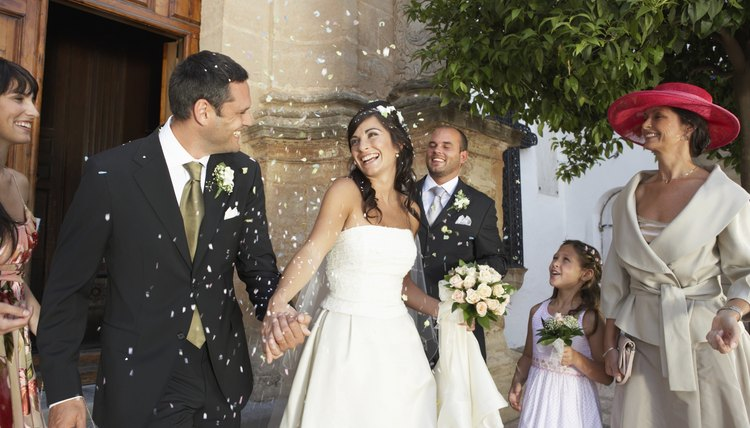 Bride and groom surrounded by falling confetti, holding hands, smiling