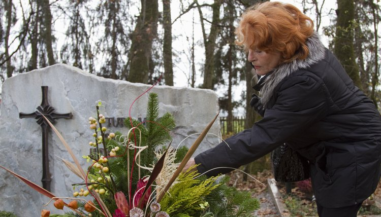 Senior woman placing flowers on grave in cemetery
