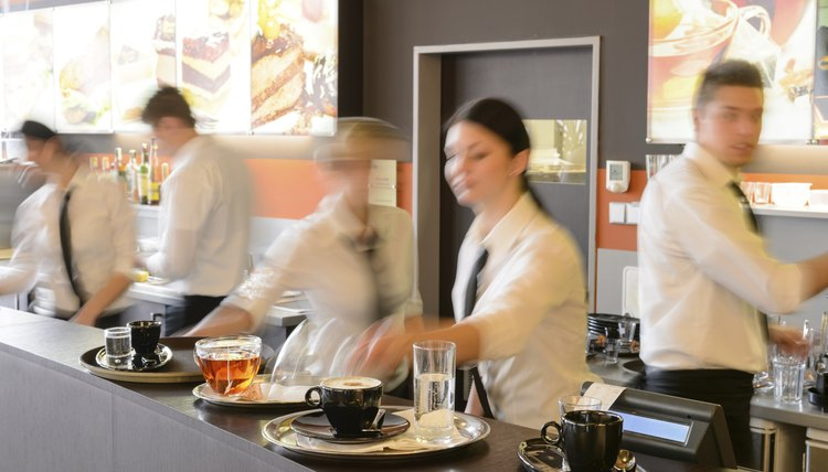 Busy waiter and waitresses working at bar