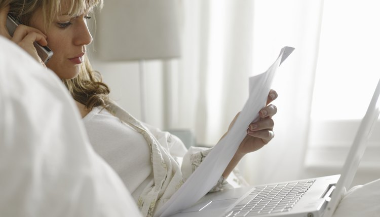 Woman lying in bed with laptop reading paperwork, using cell phone