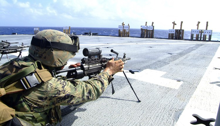A U.S. Marine adjusting his weapon on the flight deck of USS Harpers Ferry.