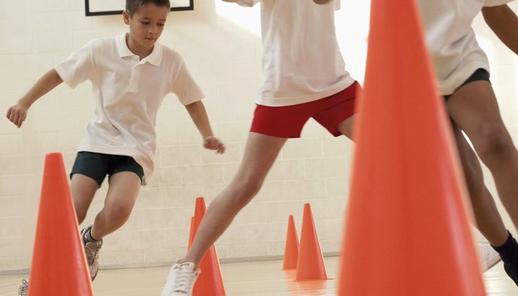 Three students run through an obstacle course in gym class.