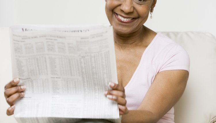 Woman holding up a newspaper.