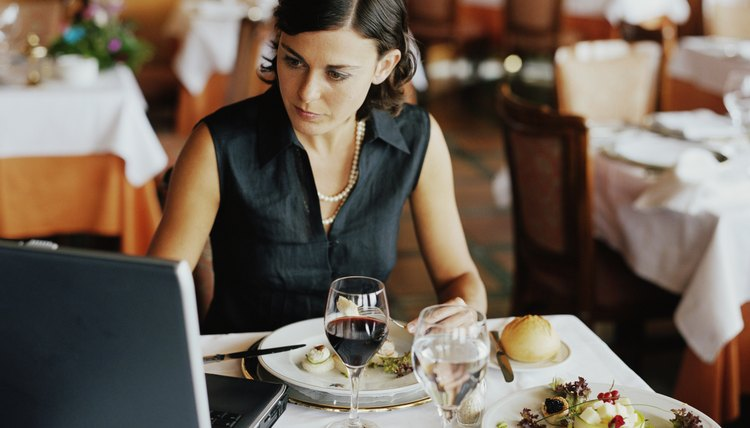 Businesswoman using laptop at restaurant table