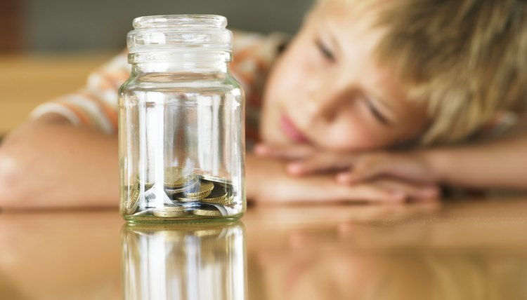 Young boy looking at jar of coins.