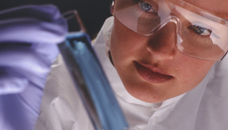 Chemist examining test tube containing liquid, close-up