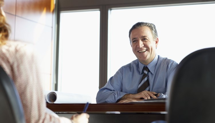Businessman at desk smiling at businesswoman, low angle view