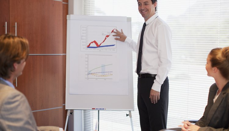 Businessman pointing to flipchart in conference room